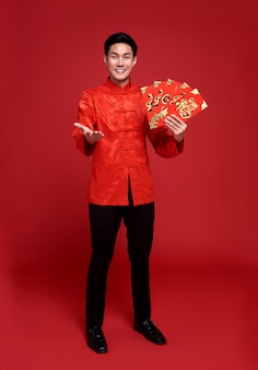 Hombre asiático que sostiene el regalo monetario del paquete rojo o angpao aislado en la pared roja.