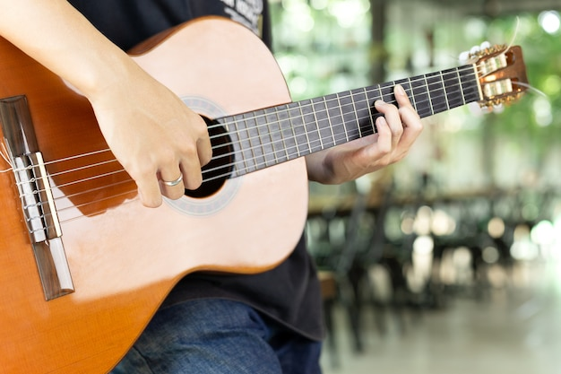 Hombre asiático que toca una guitarra clásica en fondo de la falta de definición.