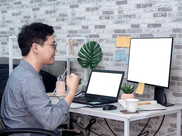 Hombre asiático que trabaja con la computadora portátil en su habitación, condominio.