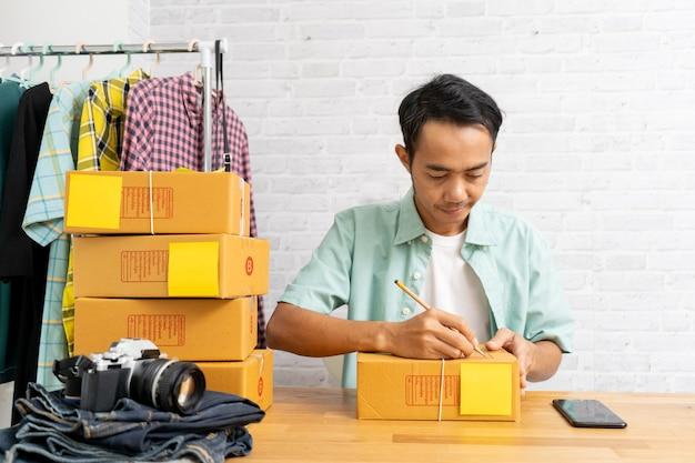 Hombre asiático que trabaja en la oficina en casa con llevar paquete marrón