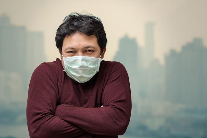 Hombre asiático que usa la mascarilla contra la contaminación del aire con frío en el balcón de high apartment