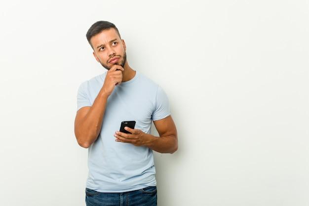Hombre asiático de raza mixta joven sosteniendo un teléfono mirando hacia los lados con expresión dudosa y escéptica.