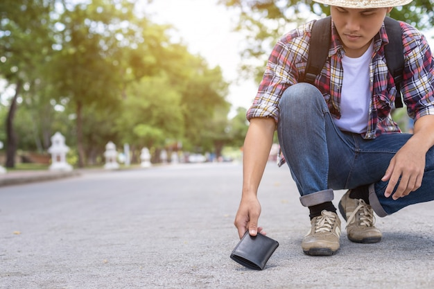 Hombre asiático recogiendo billetera negra en la carretera en atracción turística