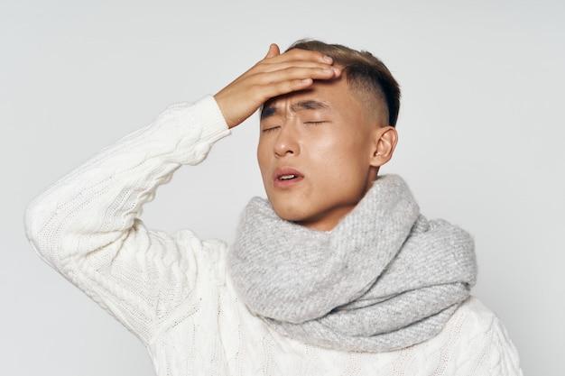 Hombre asiático en ropa de invierno cálido posando en el estudio sobre una superficie coloreada