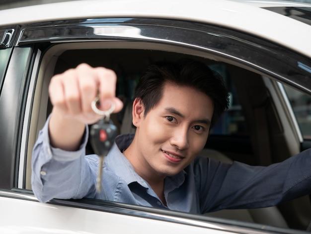 Hombre asiático sentado en coche nuevo y mostrando las llaves del coche. hombre atractivo joven que se sienta el automóvil del salón que mira hacia fuera la ventana abierta.