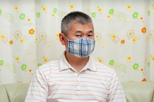 Hombre asiático sentado en el sofá con mascarilla de tela diy para protegerse contra covid19
