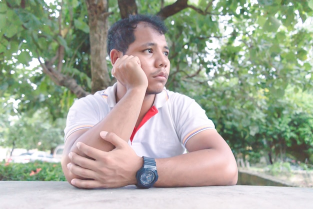 Hombre asiático se siente aburrido y decepcionado momento en el parque. concepto solo y triste.