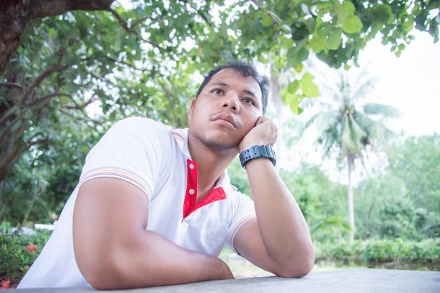 Hombre asiático se siente aburrido en el parque