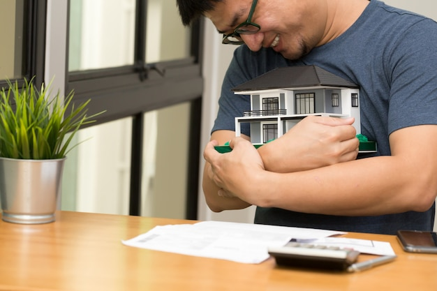Hombre asiático sonriendo y abrazando la casa de sus sueños y calcule para comprar una casa soñando en su futuro