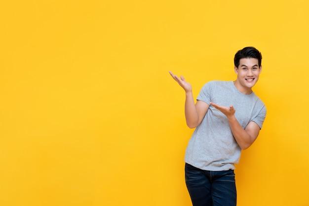 Hombre asiático sonriente que hace el gesto que presenta con las manos abiertas para copiar el espacio