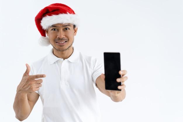 Hombre asiático sonriente que lleva el sombrero de papá noel y que señala en el smartphone