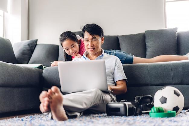 Hombre asiático sonriente que se relaja usando la computadora portátil que trabaja y la reunión de la videoconferencia chatea con su hija que aprende el libro de lectura y estudia el conocimiento en casa.