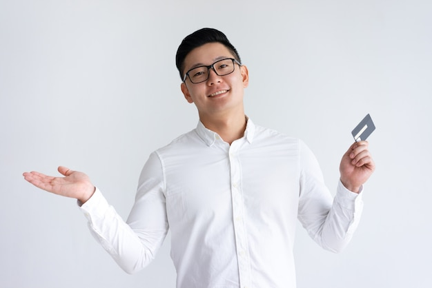 Hombre asiático sonriente que sostiene la tarjeta de crédito y que levanta la mano