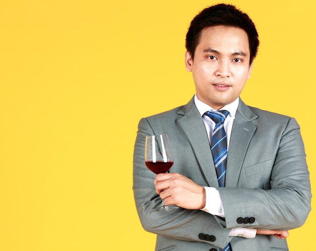 Hombre asiático sonriente sosteniendo una copa de vino para celebrar el mejor día es el día de la boda en fondo amarillo en el estudio. concepto de celebración amor encantador.