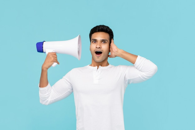Hombre asiático sorprendido escuchando voz en megáfono