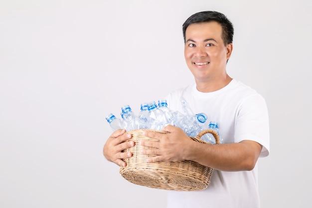 Hombre asiático sosteniendo la cesta de botellas de agua claras vacías