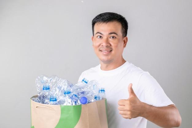 Hombre asiático sosteniendo muchas botellas de agua claras vacías