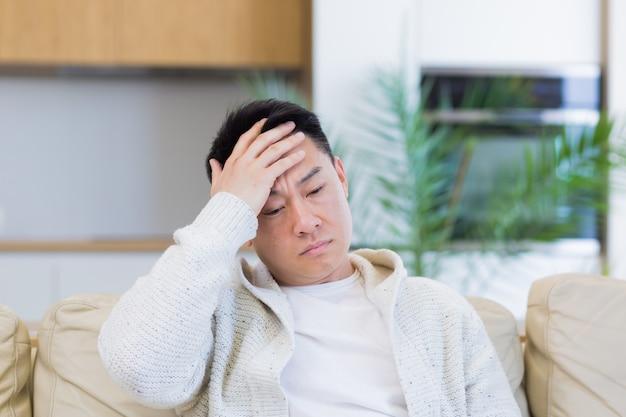 Hombre asiático sosteniendo su cabeza con un fuerte dolor de cabeza en casa en una habitación en el sofá