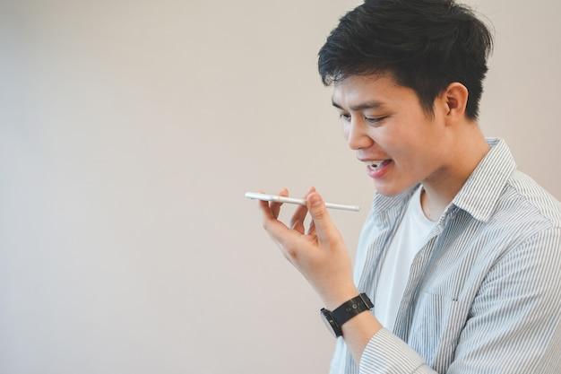 Hombre asiático sosteniendo un teléfono inteligente y hablando mediante el uso de la función de control de voz para llamadas con otros