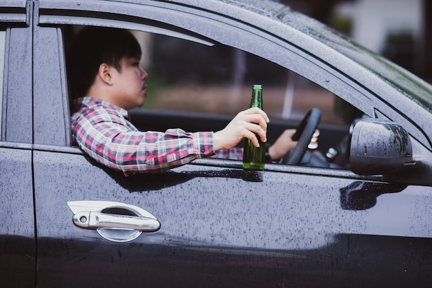 Hombre asiático sostiene una botella de cerveza mientras conduce un automóvil