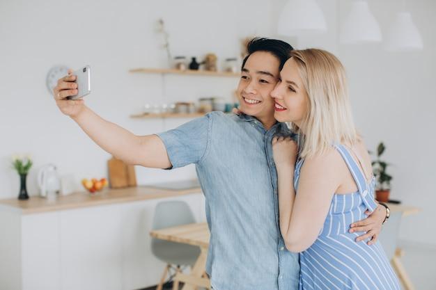 El hombre asiático y su mujer rubia caucásica pasan tiempo juntos y se hacen selfie en la cocina