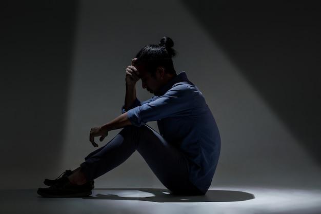 Un hombre asiático sufre de depresión en la oscuridad.