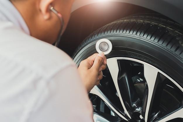 Hombre asiático, tenencia, estetoscopio, inspección del coche, neumáticos de goma, car., cierre, mano