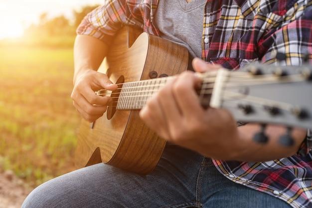 Hombre asiático tocando la guitarra en el campo de arroz verde en la hora del atardecer