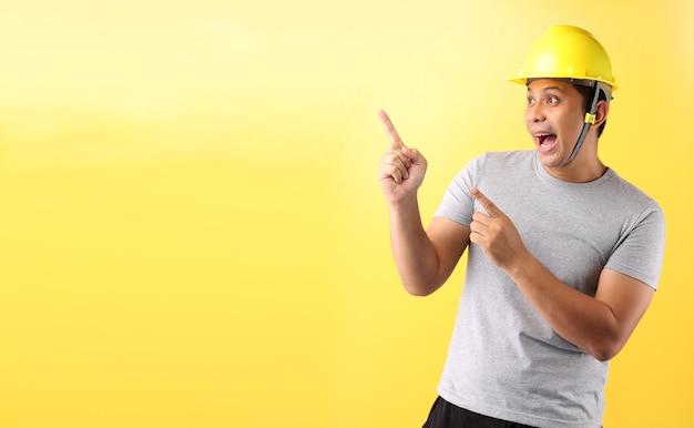 Hombre asiático trabajador de la industria o ingeniero que trabaja un arquitecto constructor dedo acusador sobre fondo amarillo.