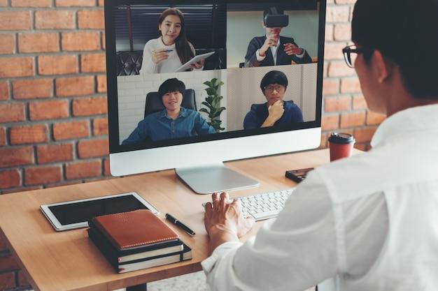 Hombre asiático trabajando desde casa y con videollamada