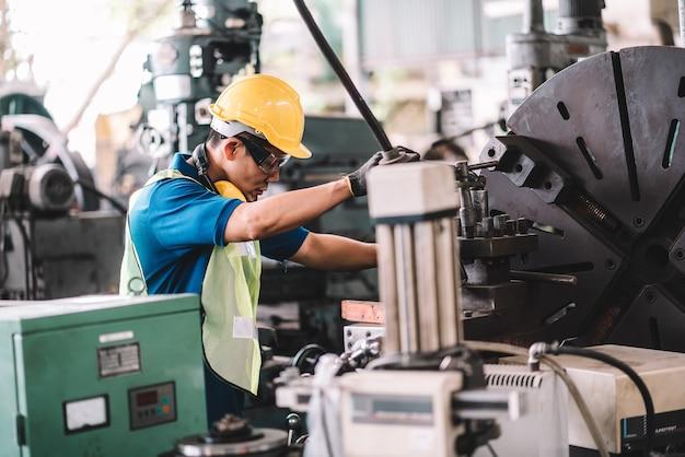 Hombre asiático trabajando en una fábrica con casco amarillo en