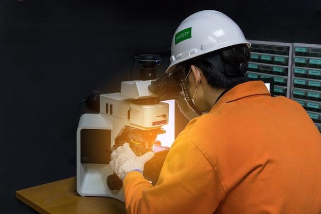 Hombre asiático en traje naranja con equipo de seguridad utilizado microscopio de vidrio de calidad en cuarto oscuro de laboratorio de control de calidad