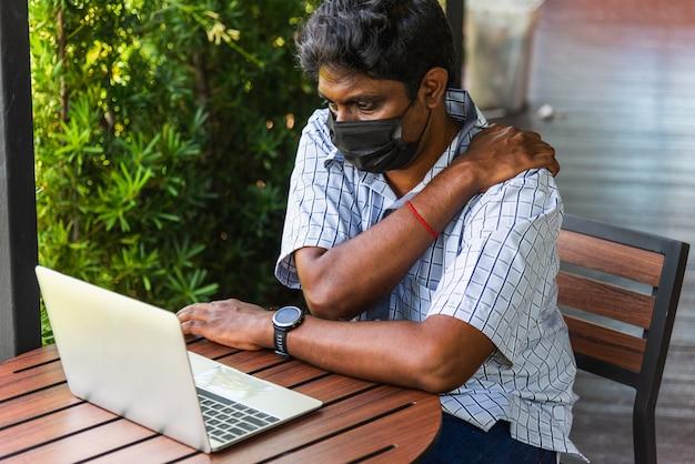 Hombre asiático usa la mano que sostiene el hombro del quiropráctico dolor de cuello muy fuerte por usar una computadora portátil