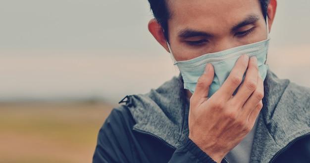 El hombre asiático usa una máscara quirúrgica o una máscara facial para proteger el virus corona 2019 o covid 19 en público