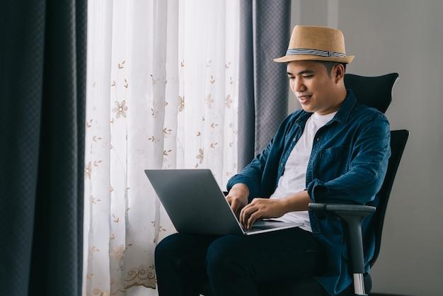 Hombre asiático usa su computadora portátil para trabajar en línea junto a la ventana, concepto de trabajo desde casa