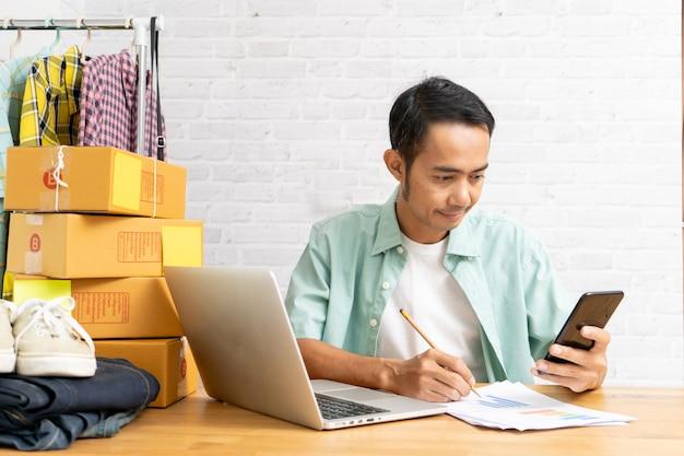 Hombre asiático utilizando teléfonos inteligentes trabajando en la oficina en casa