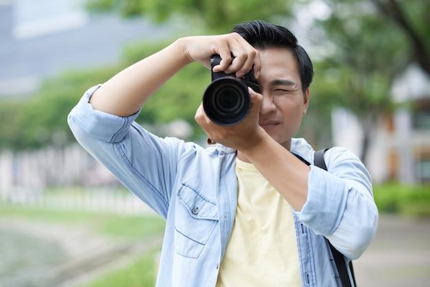 Hombre asiático vestido informalmente tomando fotos en el parque