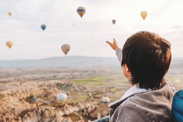 Hombre asiático viendo coloridos globos aerostáticos volando sobre el valle en capadocia, turquía este tiempo romántico