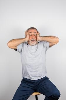 Hombre asombrado envejecido con las manos en la cabeza en silla
