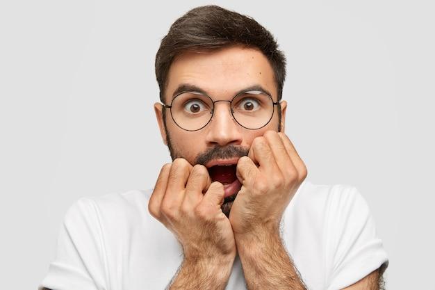 Hombre asustado sin afeitar muerde nerviosamente los puños, abre ampliamente los ojos, se siente ansioso, tiene miedo de algo aterrorizado, usa anteojos redondos y camiseta blanca