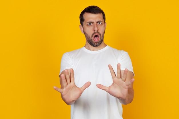 El hombre asustado extendió las manos al frente con un gesto de parada