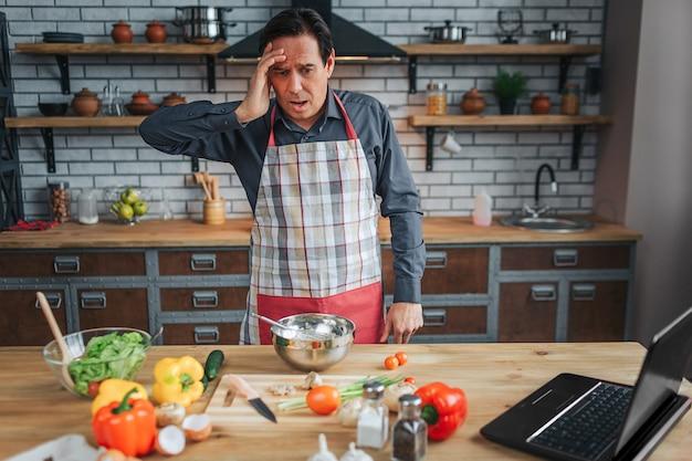 Hombre asustado se para a la mesa en la cocina y lo mira. él toma la mano sobre la cabeza. delantal de hombre. verduras coloridas en el escritorio.