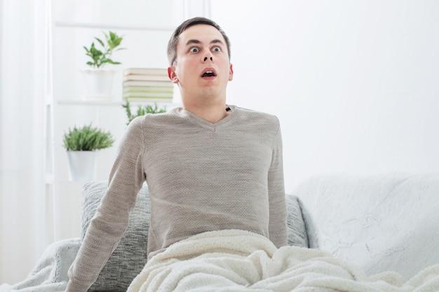 Hombre asustado en el sofá