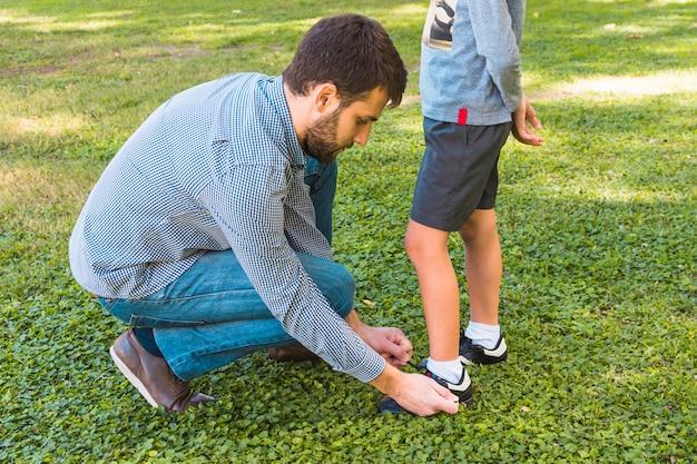 Un hombre atando el cordón de su hijo en el parque.