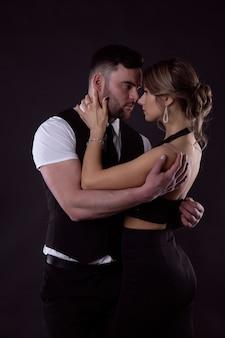Un hombre en un ataque de pasión desabotona el vestido de una mujer joven