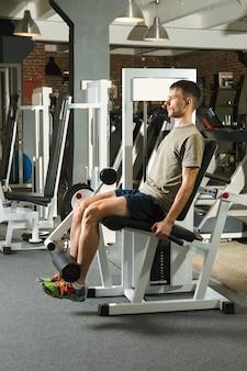 Hombre atelético balancea los músculos abdominales en el gimnasio.