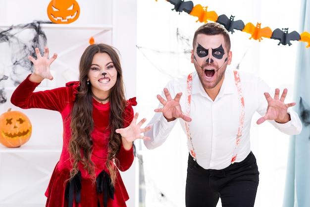Hombre aterrador y niña en disfraces de halloween