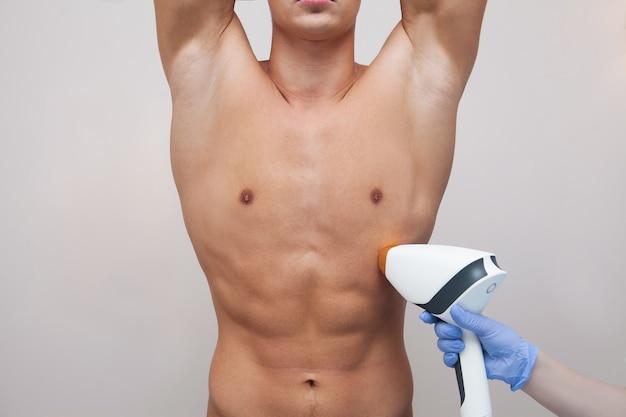 Hombre atleta musculoso sosteniendo sus brazos hacia arriba y mostrando las axilas, la axila suave piel clara. depilación y depilación del cabello en salón de belleza. concepto de depilación láser masculino