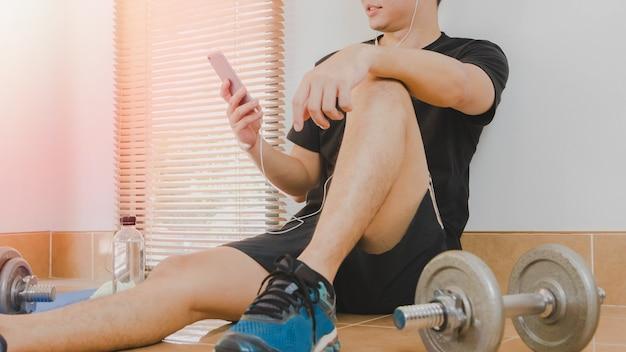 El hombre de atletas asiáticos está descansando después de hacer ejercicio