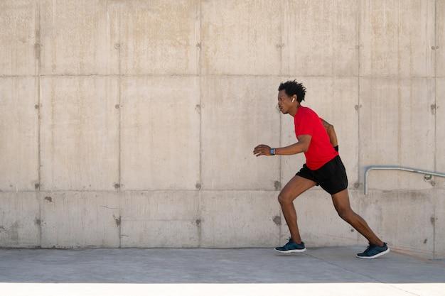 Hombre atlético afro corriendo y haciendo ejercicio al aire libre en la calle. concepto de deporte y estilo de vida saludable.